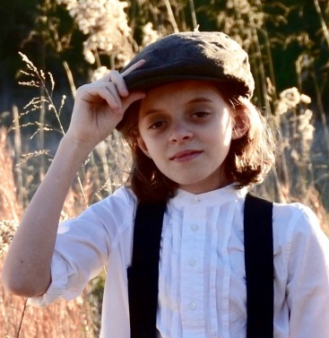With a field near the Santa Fe Trail in the background, Grace Willis, protagonist, tips her hat. She is dressed as a boy in a white shirt with braces, typical of the late 1850s.